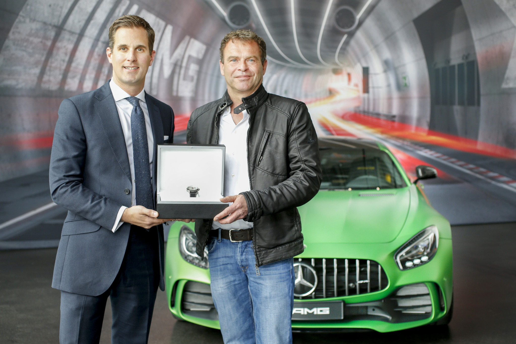 """IWC CEO Christoph Grainger-Herr visits the AMG manufacture in Affalterbach and hands over the Ingenieur Chronograph Sport Edition """"50th Anniversary of Mercedes-AMG"""" to AMG CEO Tobias Moers."""